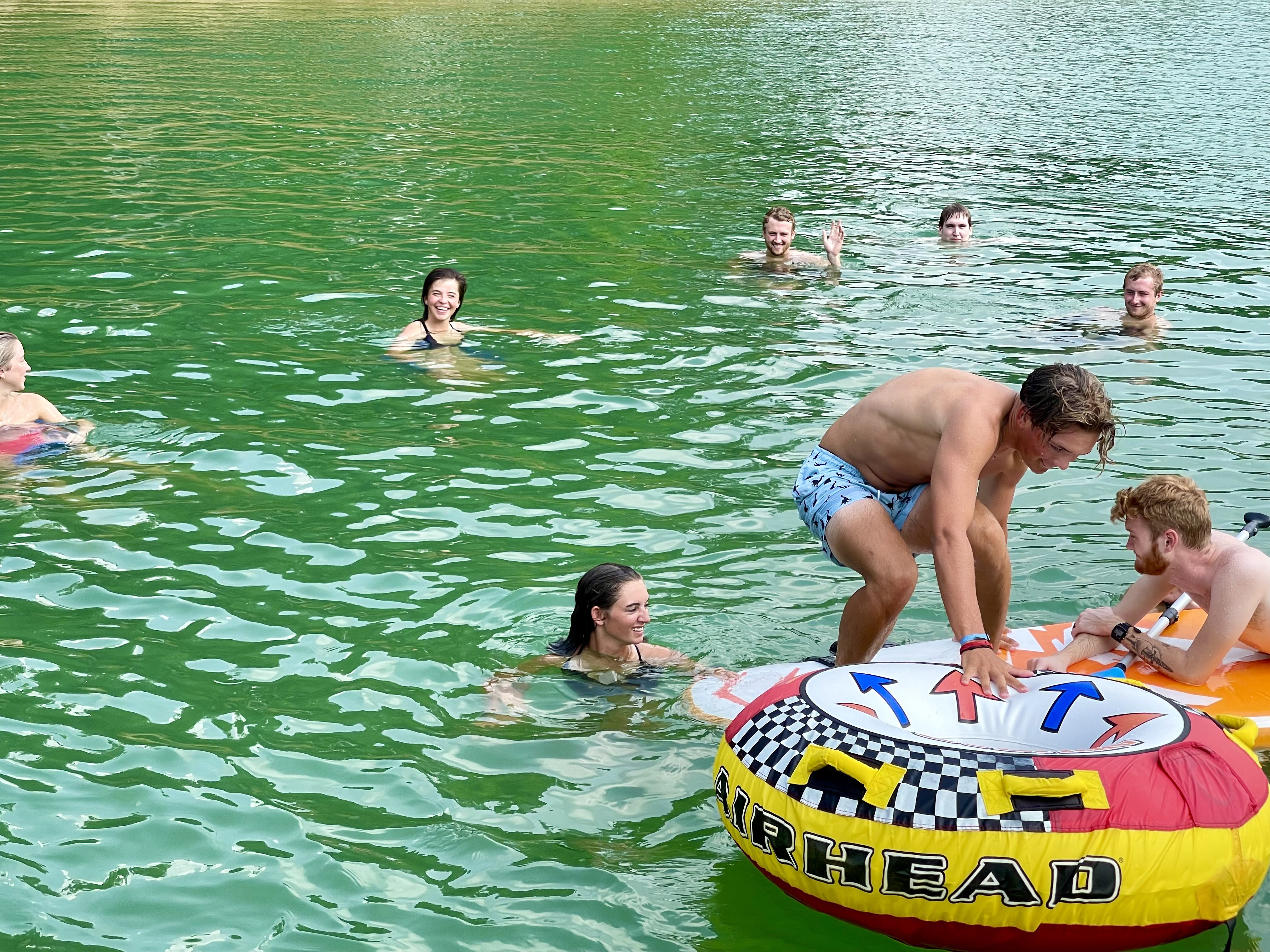 young adults playing at the lake on a water tube