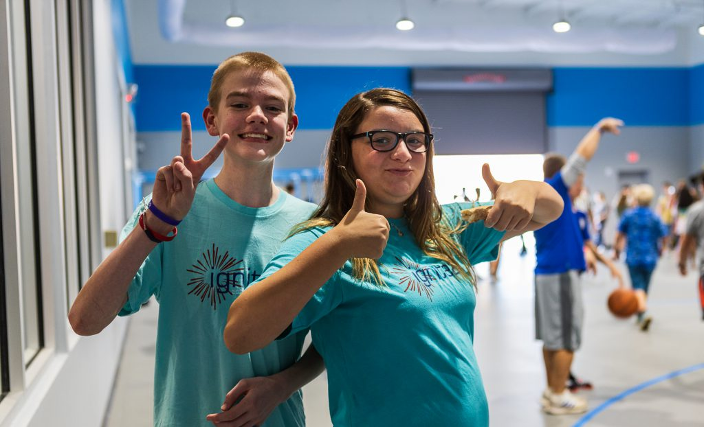 young adults expressing themselves with thumbs up and peace signs